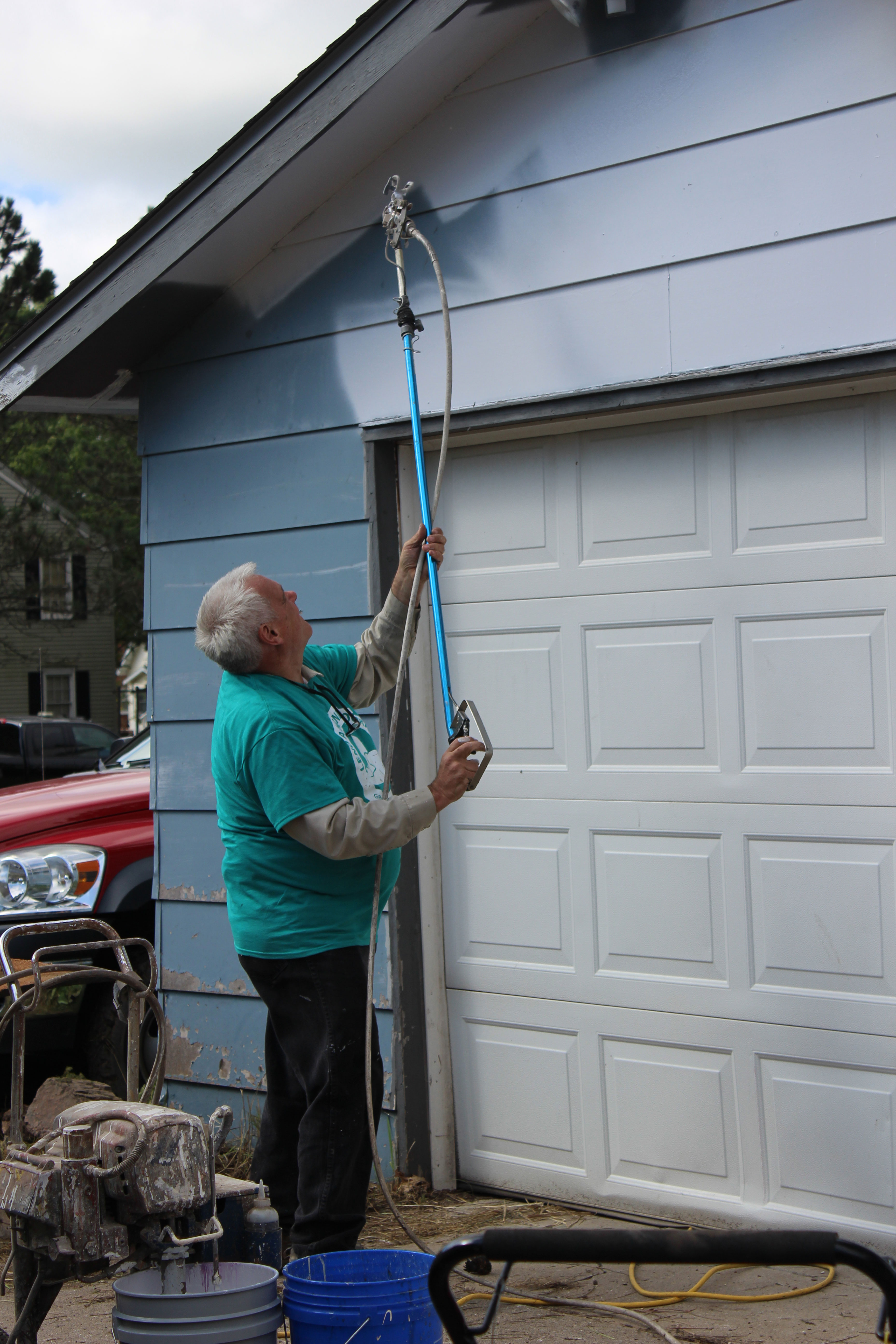 Facilities Associate, Curt Neumann paints the side of the garage